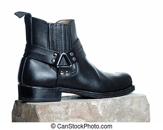 Bootee - The picture shows a black bootee on a brick