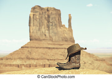 Boots and hat in front of Monument Valley
