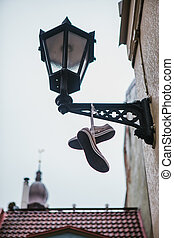 Boots hang on the old lamp. Creative idea. Decoration of the house