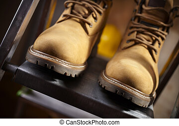 boots of constructor - shoes on metal stepladder,selective...