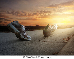 Boots walking - A pair of boots walk down the road at sunset