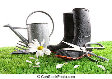 Boots with watering can and daisy in grass