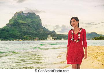 Bora Bora luxury vacation beautiful Asian tourist woman on Tahiti French Polynesia cruise ship travel adventure. Girl smiling wearing lei flower necklace on sunset beach walk