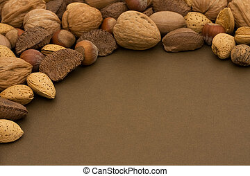 Border frame of healthy mixed nuts in shell on a brown background, healthy eating