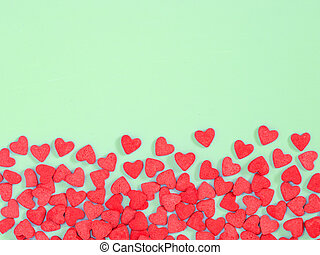 Border frame of red hearth-shape sprinkle on green background