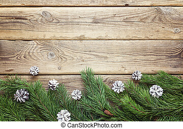Border from fir branches with white cones on a old wooden boards. Christmas background. Space for text.