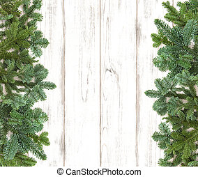 Border from pine tree branches on wooden background