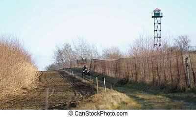 Border guards on ATV make inspection border in the winter season. The border area between Ukraine and Poland. Two border guards ATV. State border with a fence and plowed land.