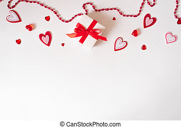 Border of a gift with a red bow, beads, glass and felt hearts on a white background