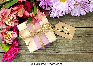 Border of flowers with gift box and Happy Mothers Day tag against rustic wood