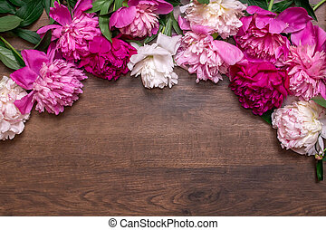 Border of peonies on a wooden background. Floral design. Pink and purple spring flowers.