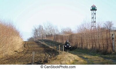 Border Patrol agents ride along and watch the fence line for illegal immigrants and drug traffic. Border patrol on a quad bike on the border. Two border guards ATV.