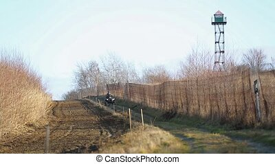 Border guards on ATV patrols state border. State border with a fence and plowed land. Two border guards ATV.