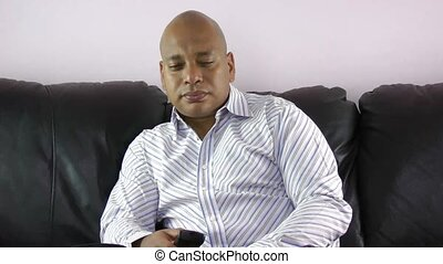 Bored african businessman watching tv