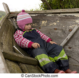 Bored and upset child (3 years old) sitting in an old boat.