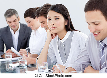 Bored asian businesswoman in a meeting with her team