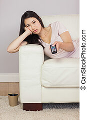 Bored asian girl lying on the sofa watching tv