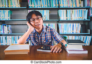 Bored asian student with books in library