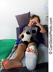 Bored boy with a broken leg sitting on the couch and holding a football ball.