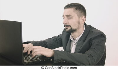 Bored businessman typing at his desk