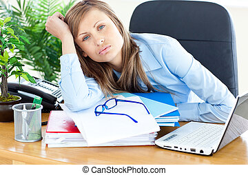 Bored businesswoman sitting at her desk