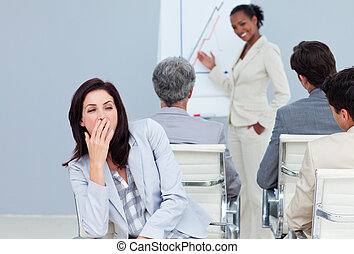 Bored businesswoman yawming at a presentation with her ...