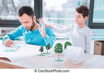 Bored child disturbing his dad