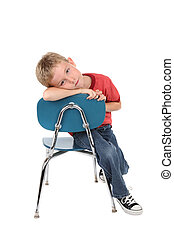 Bored child - A young hangs on the back of his school chair