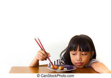 Bored children girl with red chopsticks sitting at the table