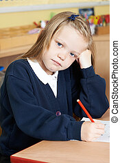 Bored Female Elementary School Pupil At Desk