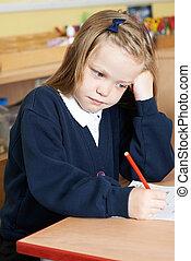 Bored Female Elementary School Pupil At Desk