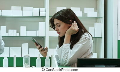 Bored female pharmacist use mobile phone at pharmacy