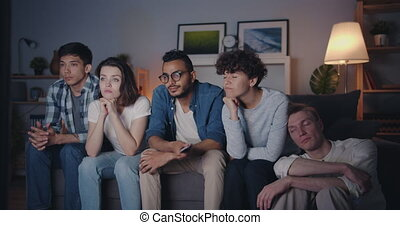 Bored friends choosing TV program clicking remote control at...