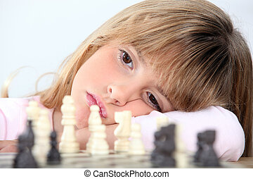Bored girl playing chess