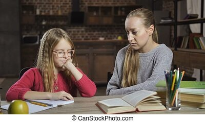 Bored girl unwilling to do homework with mother
