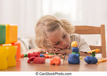 Bored girl with plasticine toys - Bored girl leaning her...