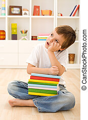Bored kid with lots of school books