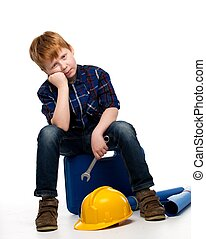 Bored little mechanic boy with wrench tools sitting on a toolbox
