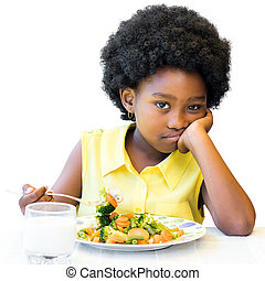Bored looking african girl sitting with vegetable dish. - ...