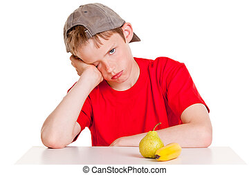 Single young boy in red shirt, backward hat and hand on cheek with bored expression sitting in front of green pear and yellow banana over white background