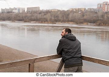 Bored man looking at the river