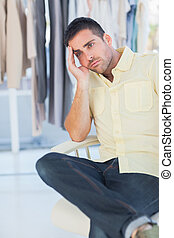 Bored man sitting in a clothing store