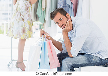 Bored man with shopping bags while woman by clothes rack -...