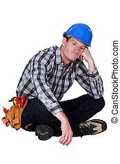 Bored manual worker sat cross-legged