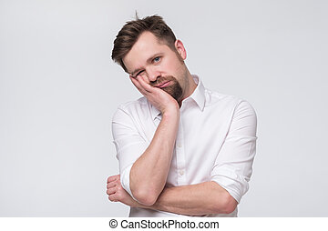 Bored mature caucasian man with beard holding hand on cheek looking tired and sick