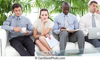 Bored multi-ethnic business people sitting on a sofa waiting...