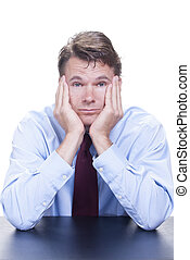 Bored - Male Caucasian office worker sits at desk with...