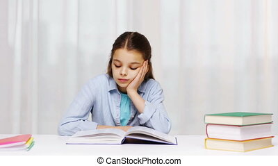 bored school girl reading book or textbook at home -...