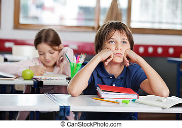 Bored Schoolboy Looking Away Sitting At Desk In Classroom -...