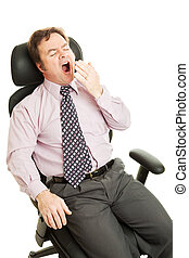 Businessman yawns in his comfortable ergonomic office chair. Isolated on white.